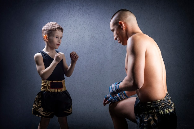 Kickboxing coach is training the boy. the concept of family, sports, mma, muay thai
