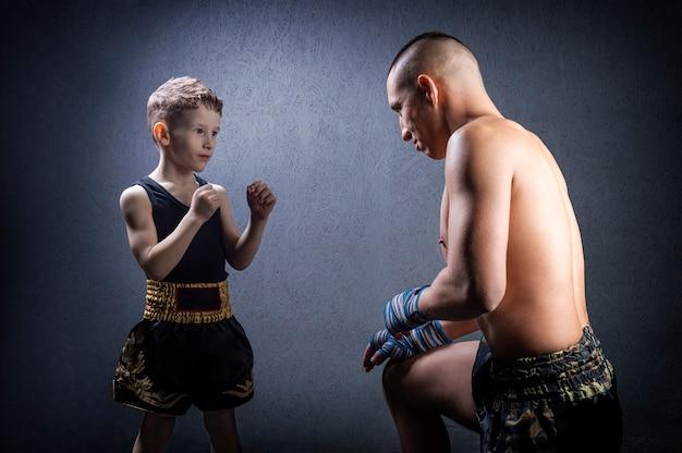 キックボクシングのコーチが少年を訓練しています。家族、スポーツ、総合格闘技、ムエタイの概念