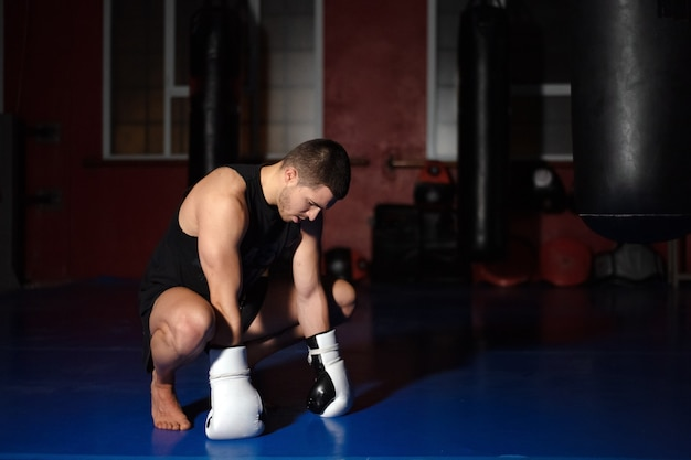 Kickboxing fighter in boxing gloves standing on knees.
