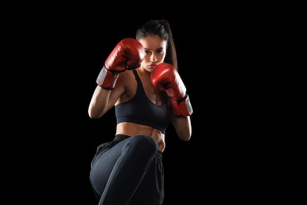 Женщина по кикбоксингу в спортивной одежде и красных перчатках для кикбоксинга на черном фоне, выполняя удар боевых искусств. спортивные упражнения, фитнес-тренировки.