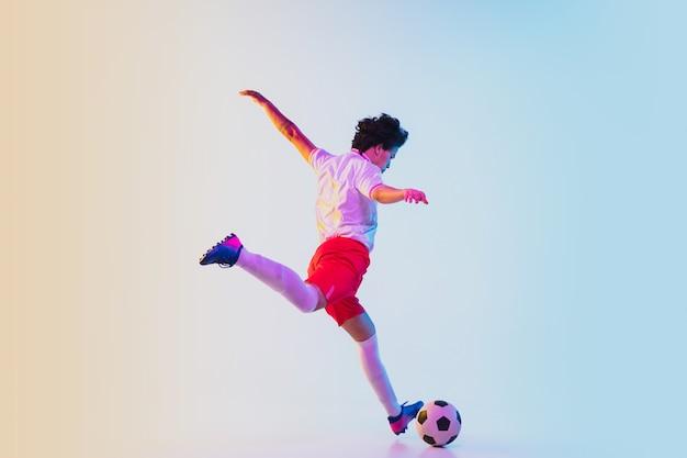 Пинается в прыжке, на бегу. футболист или футболист на градиентном фоне в неоновом свете - движение, действие, активность. понятие спорта, соревнования, победы, действия, движения, преодоления. copyspace.
