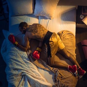 Удар ногой. вид сверху молодого профессионального боксера, борца, спящего в своей спальне в спортивной одежде с перчатками. любить спорт даже больше, чем комфорт, играть в матче, даже если отдыхает. действие, движение, юмор.