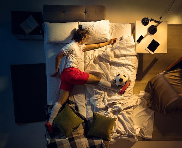 Удар ногой. вид сверху молодого профессионального футболиста, футболиста, спящего в своей спальне в спортивной одежде с мячом. любящий спорт, трудоголик, играющий в матч, даже если отдыхает. действие, движение, юмор.