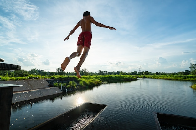 Kid in the air while jumping into lake with nice sunray - summer nature scenery