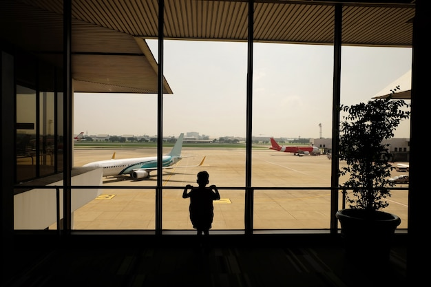 Kid at airport waiting for departure , color filter image , business travel airport