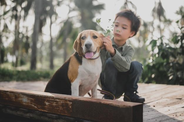 Образ жизни малыша и собаки в парке. маленький мальчик вместе с домашним животным как лучший друг. активный отдых на летнем отдыхе.