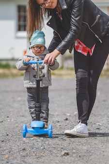 Малыш и мама играют на скутерах на свежем воздухе.