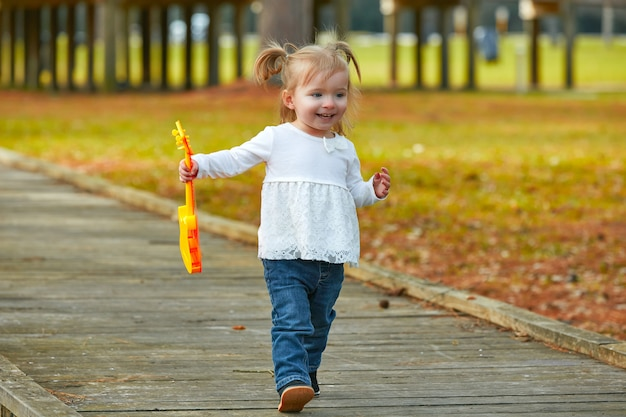 Kid baby girl with toy guitar walking in park