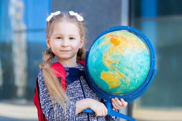 Малыш снова в школу. умная уверенная в себе девочка пошла в первый класс. умный школьник держит глобус. образование.