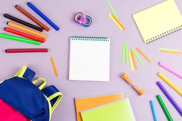 Детский рюкзак, тетради, маркеры на деревянном столе, вид сверху