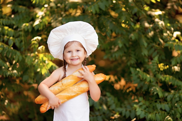 Kid baker at picnic eating bread and bagels in white apron and hat