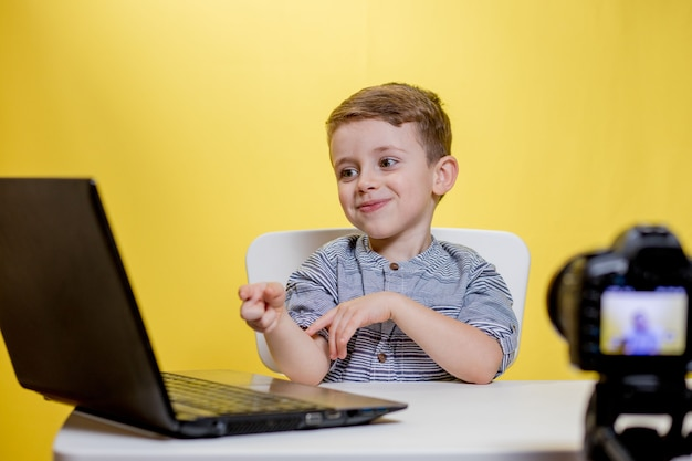 自宅で、ラップトップで動作するカメラでビデオを撮影する子供のブロガー