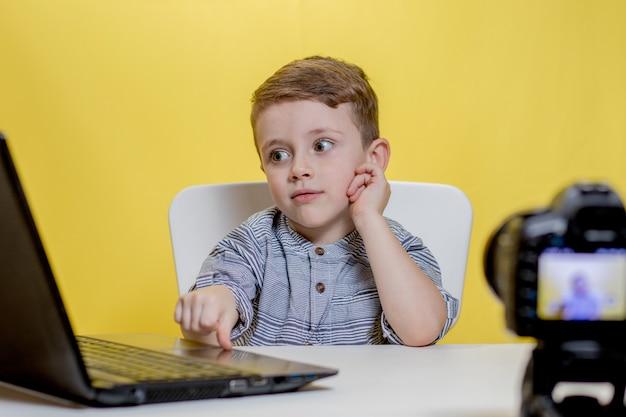 ノートパソコンで動作するカメラでビデオを撮影する子供のブロガー