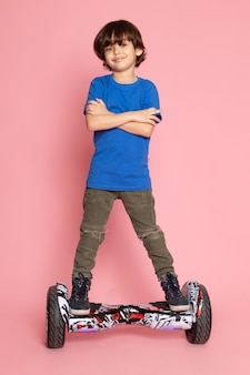 Kid in blue t-shirt riding segway on pink
