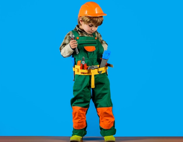 Kid boy in builders uniform and helmet with repair tools, child game, little boy plays construction worker.