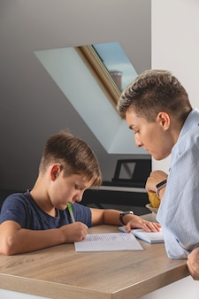 Kid boy doing homework at kitchen table with book