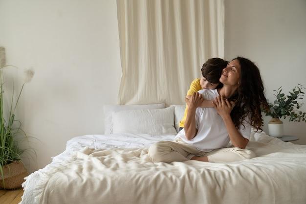 어린 소년은 주말 가족 사랑에 집에서 잠옷을 입고 침대에 앉아 아침에 웃는 엄마를 껴안습니다.