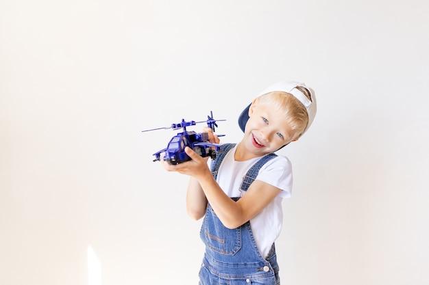 Малыш мальчик в синих джинсах играет с вертолетом