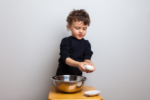 Kid, boy learns to wash his hands with soap. hand disinfection.