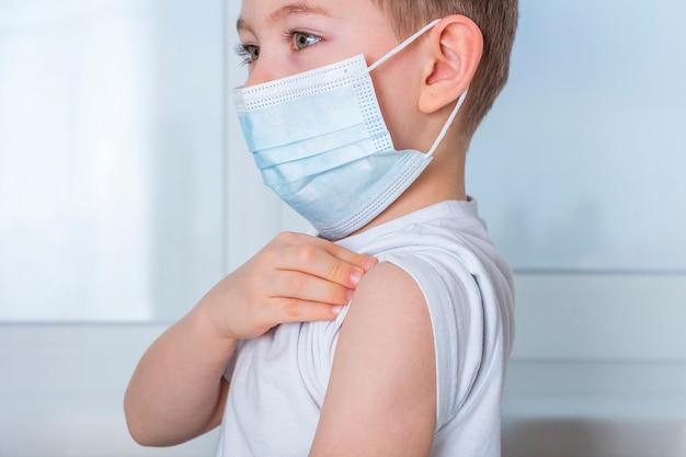 子供の男の子は予防接種を受けるために腕のtシャツの袖を持ち上げます。