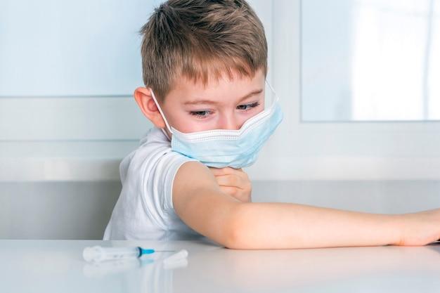 子供の男の子は、ワクチン接種を受けるために腕のtシャツの袖を持ち上げます。