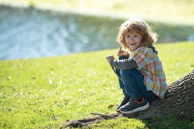 屋外の子供の男の子。公園の子供たち。木の横にある春の少年。夏の散歩。子供の適応。