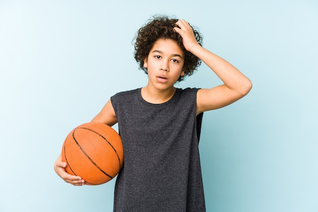Kid boy playing basketball isolated on blue background being shocked, she has remembered important meeting.