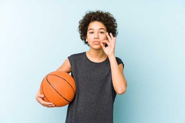 Kid boy playing basketball isolated on blue background with fingers on lips keeping a secret.