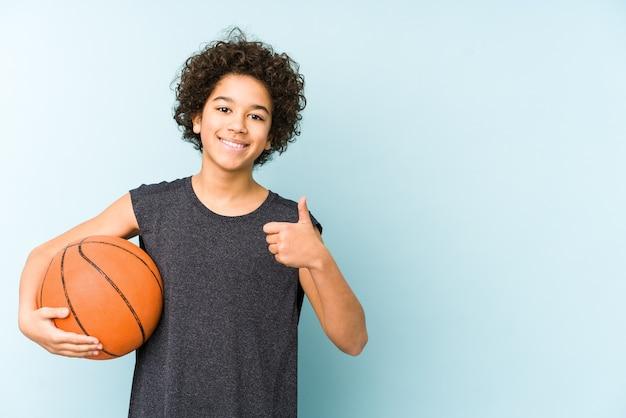 Малыш мальчик играет в баскетбол, изолированный на синем, улыбаясь и поднимая палец