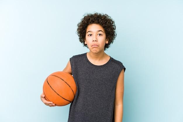 Малыш мальчик играет в баскетбол, изолированные на синей стене, пожимает плечами и смущает открытые глаза.