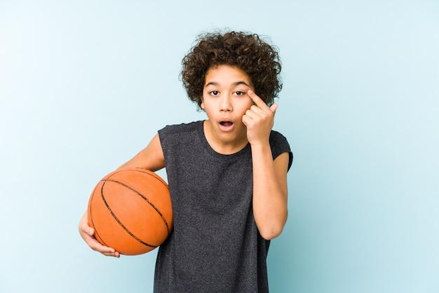 Оягнитесь мальчик играя баскетбол на голубой стене показывая жест разочарования с указательным пальцем.