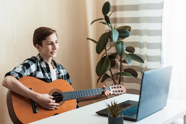 Kid boy playing guitar and watching online lessons on laptop while practicing at home. stay home. quarantine. online training, online classes