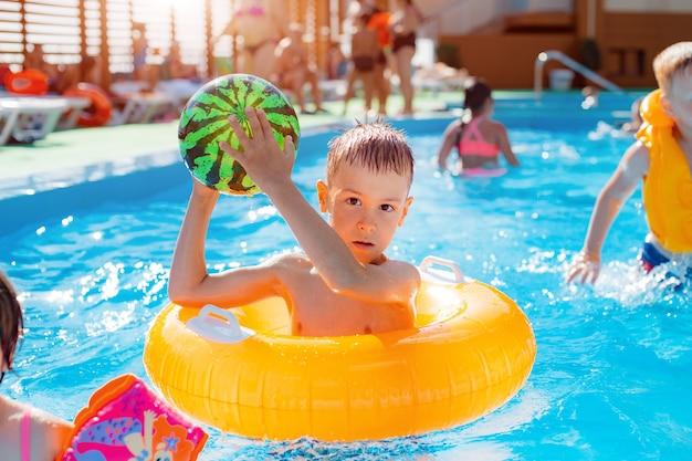 リゾートの屋外プールで遊ぶ男の子。ボールで膨らませて黄色い円で。水のおもちゃで戯れる子供たち。飛び散る。熱を冷やす。