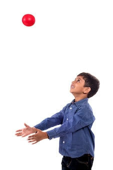 Kid boy playing with ball on white wall