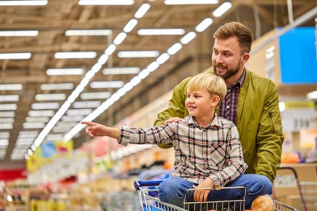 父親と一緒に買い物をしているときに店の横に人差し指を向ける子供の男の子、子供は食料品のスーパーマーケットで時間を楽しんで、楽しいカートに座っています