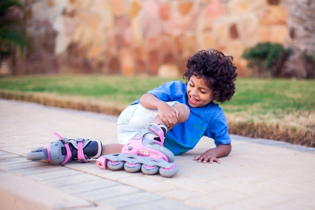 A kid boy on rollerskates fell down and feels pain. children, leasure and healthcare concept