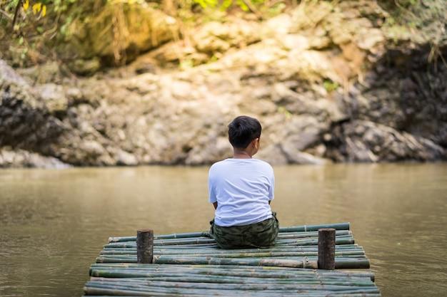 Kid boy sit on the bamboo bridge beside the lake
