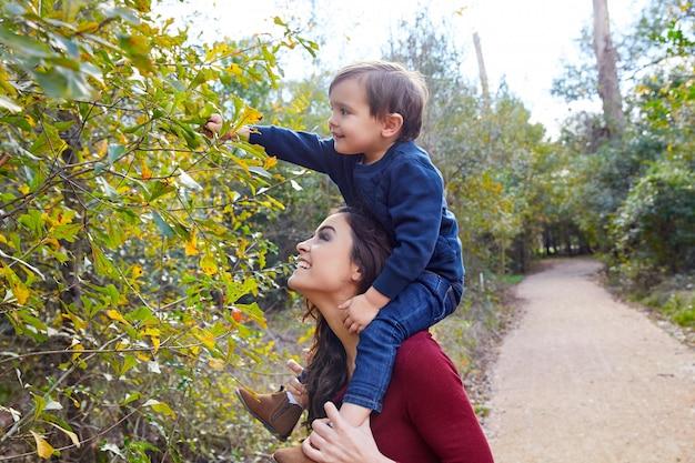 Kid boy sit on mother shoulders picking leave