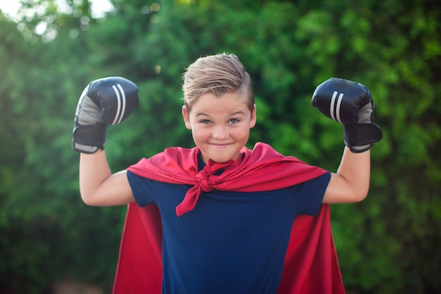 Kid boy superhero with boxing gloves and red cloak
