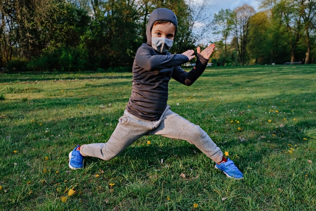 Kid boy wearing like ninja does different exercises outdoor