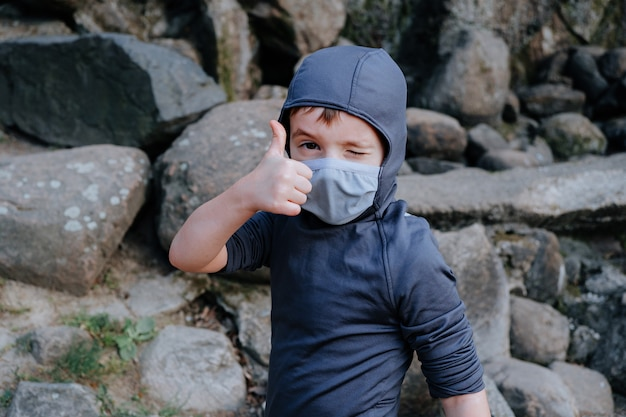 Kid boy wearing like ninja winks and points his thumb up