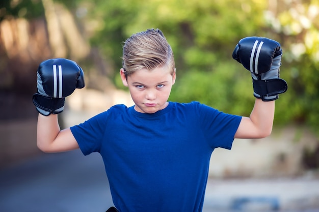 Kid boy with boxing gloves showing strong outdoor