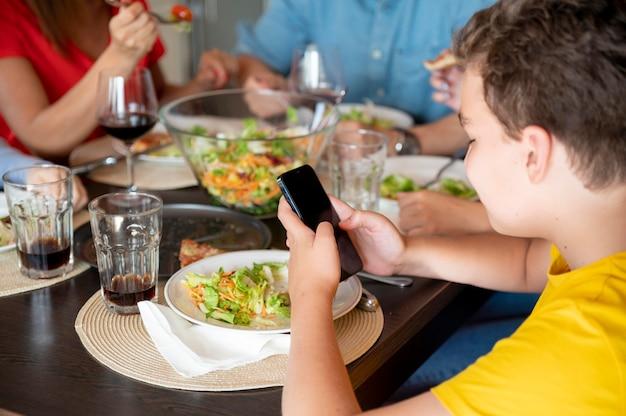 Bambino che naviga sul suo smartphone mentre è a cena in famiglia