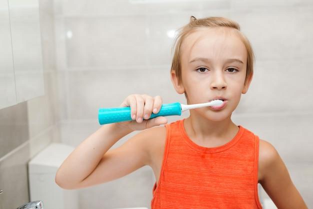 욕실에서 전기 브러시로 양치질하는 아이. 매일 치과 위생. 건강 관리, 어린 시절 및 치과 위생. 소년은 치아의 건강에 관심이 있습니다. 치아를 청소 하는 행복 한 소년.