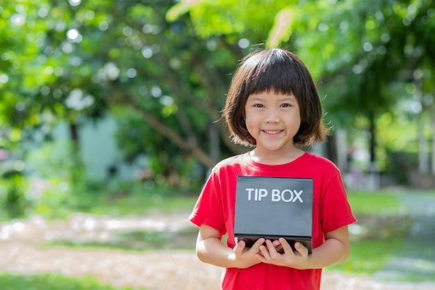 子供のキャリーチップボックスを手に自然の背景をぼかし