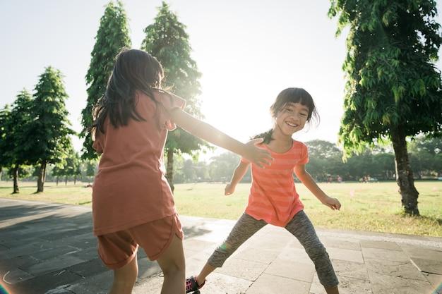 아이는 친구와 함께 야외에서 잡고 놀기