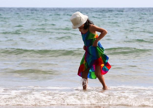 ビーチの幸せで水からスカートをキャッチし、夏の時間をリラックスする子供