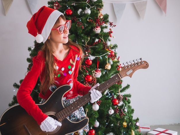 Kid celebrate christmas by struming the guitar in house, a girl plays a song with a smile on christmas day