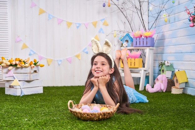 Kid celebrate easter. funny happy baby in bunny ears playing with easter eggs