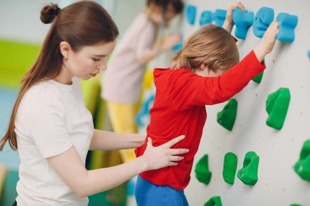 벽을 등반하는 아이 아이. 어린이 스포츠, 유치원의 건강한 생활 방식 또는 학교의 스포츠 센터.